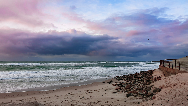Naturbilde av hav med rosa skyer