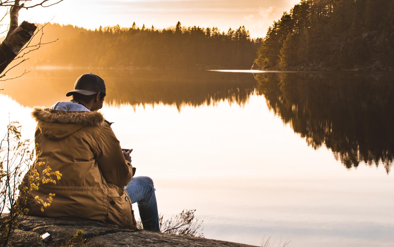 Bilde av mann med ryggen mot kameraet. i bakgrunnen ser man solnedgangen.