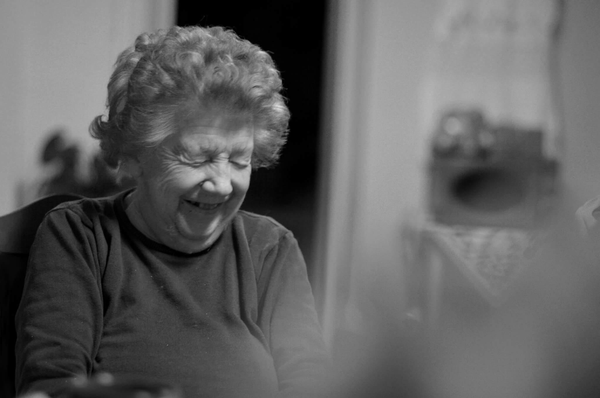 Sort/hvitt bilde av eldre kvinne som ler