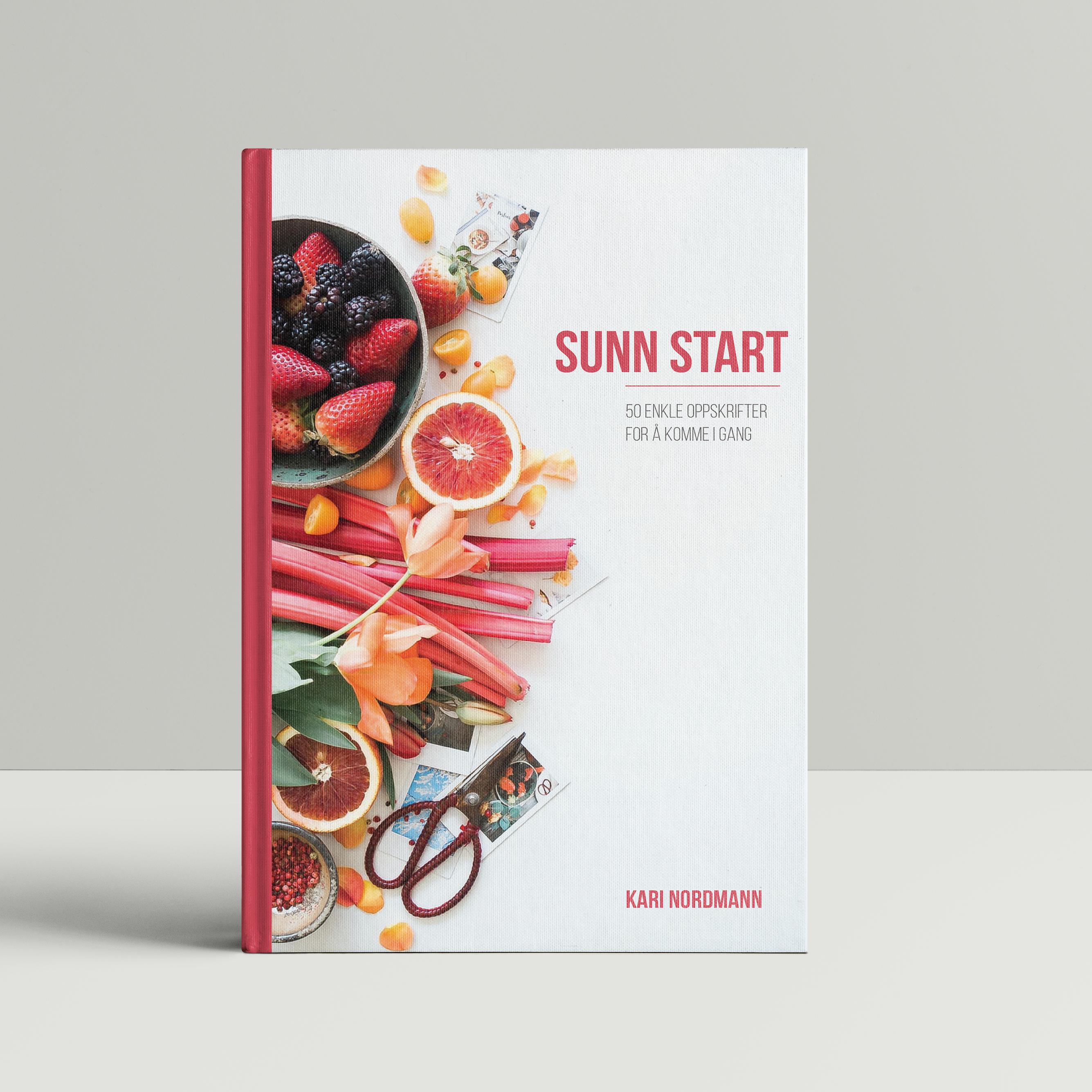 Bilde av en kokebok med hvit bakgrunn og rosa tekst. Boken har omslag med bilder av mange typer frukt.